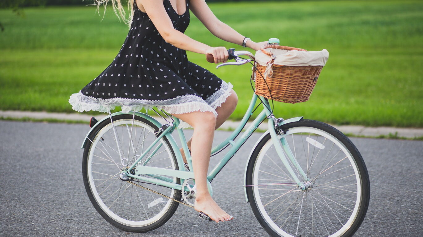 Woman in dress riding a bicyle with a front basket.